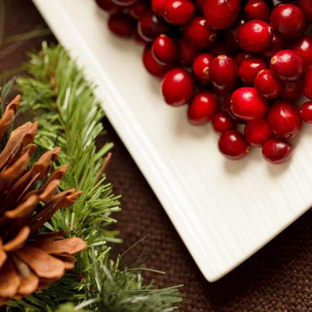 A pine cone and needles next to a plate of cranberries on a table
