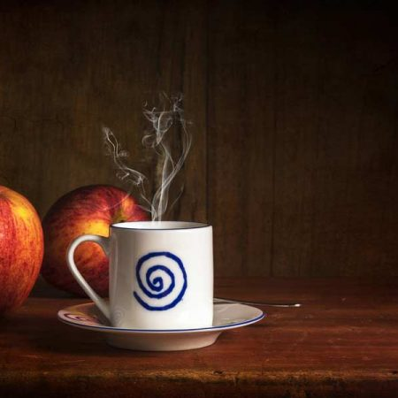 a warm mug of apple cider with fresh apples