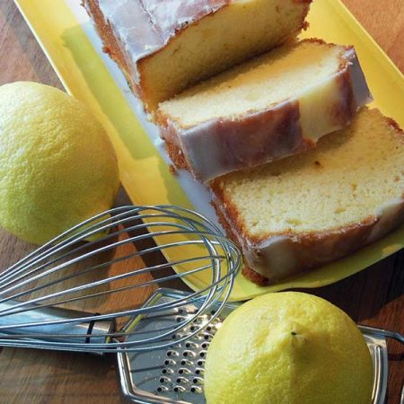 A freshly-sliced loaf of lemon pound cake covered in a sugar glaze