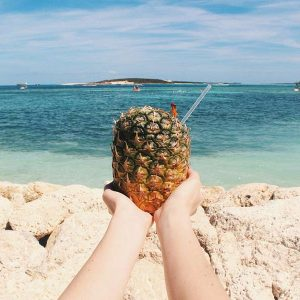 Hands holding a tropical pineapple drink on a sunny beach